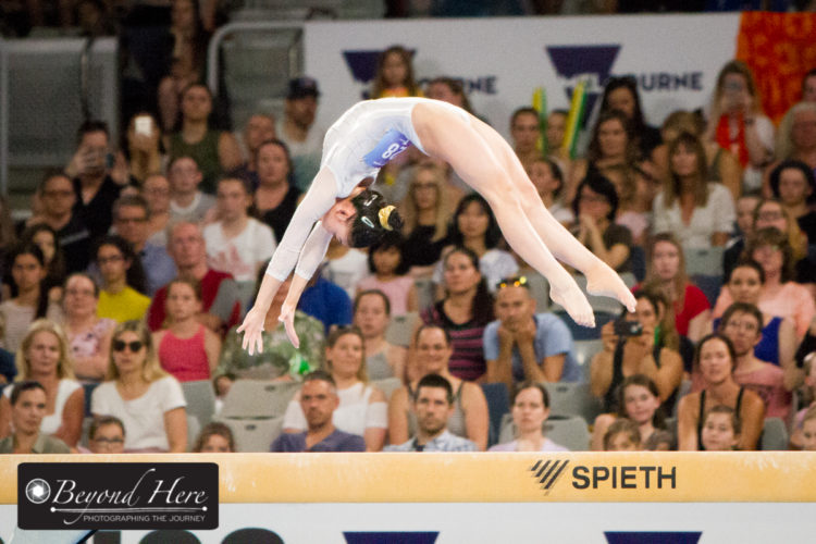 Gymnast doing back flip on beam