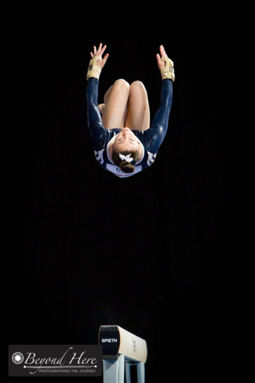 Gymnast in mid air above the beam