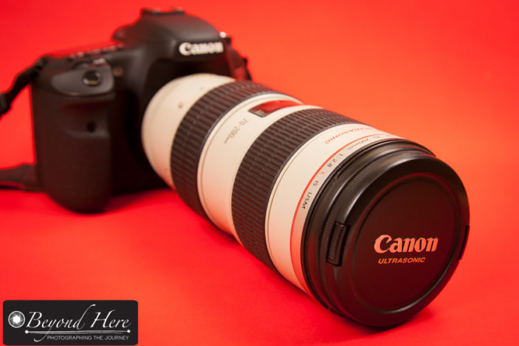 Canon 70-200mm lens on dslr with red background