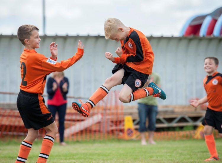 Junior football celebration. Sports photographer Sally Jacob.
